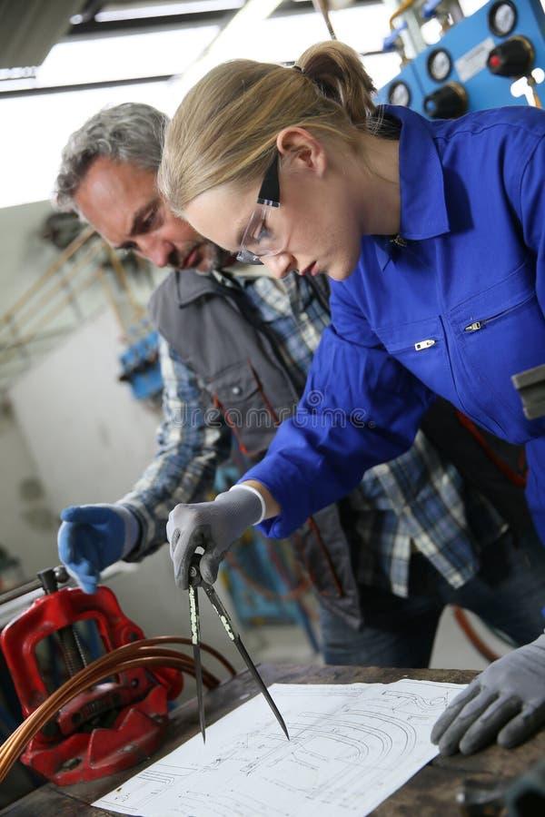 Lärling med instruktören i plumberyteckningsplan arkivbild