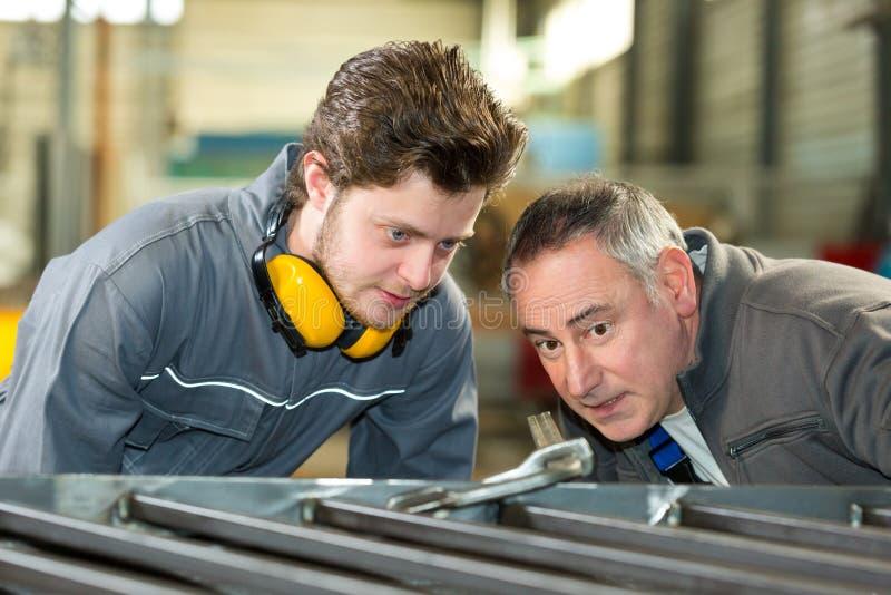 Lärling och lärare som arbetar med metallstänger i fabrik arkivfoton