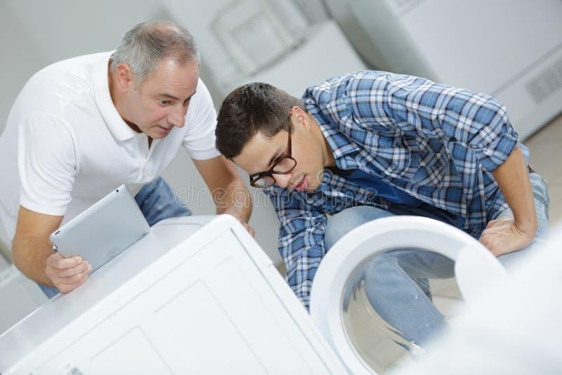 Lärlingrepairman med instruktören som reparerar tvagningmaskinen royaltyfria bilder