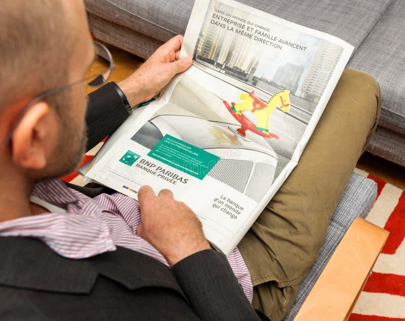 Läs- advertizing för man av den BNP Paribas banken royaltyfri fotografi