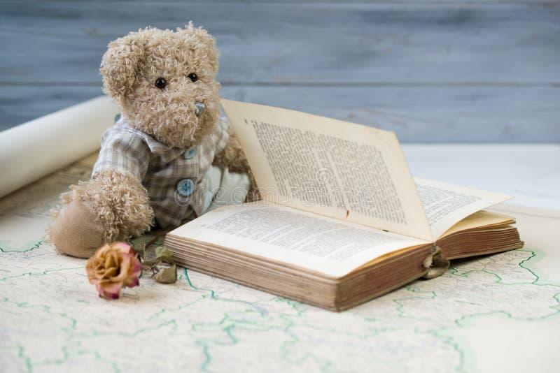 Läs- antik bok för nallebjörn på den gamla översikten royaltyfri fotografi
