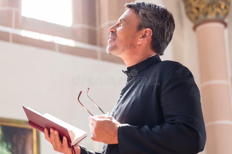 Läs- bibel för katolsk präst i kyrka fotografering för bildbyråer