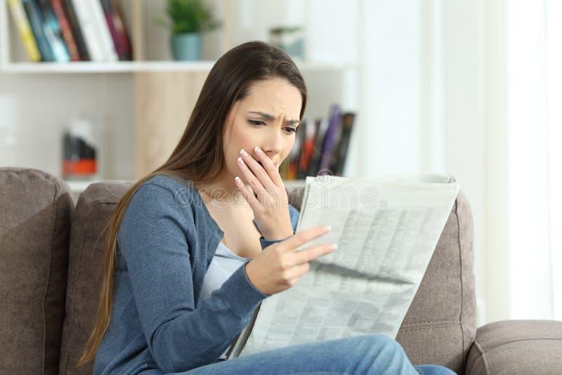 Läs- dåliga nyheter för bekymrad kvinna i en tidning hemma arkivbild