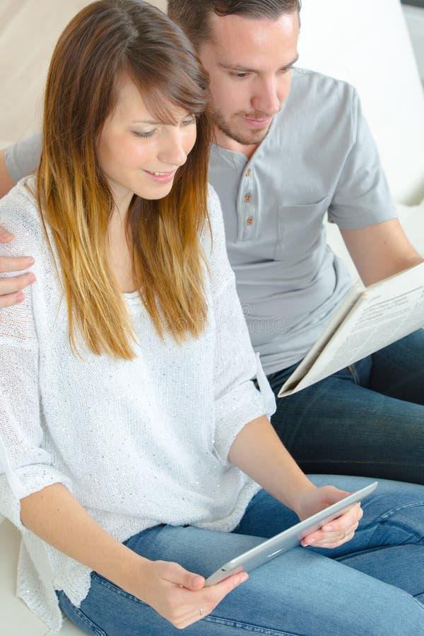 Läs- eBooks för barnpar på soffan hemma royaltyfri foto