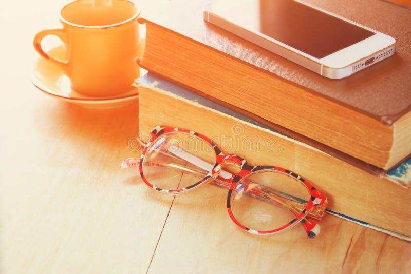 Läs- exponeringsglas, bunt av gamla böcker och smartphone över trätabellen, retro filtrerad bild arkivfoto