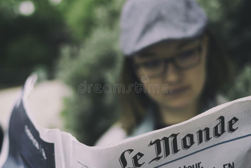 Läs- fransk tidning för kvinna, Le Monde royaltyfri bild