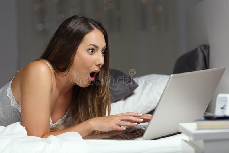 Läs- goda nyheter för häpen kvinna direktanslutet i natten royaltyfria foton