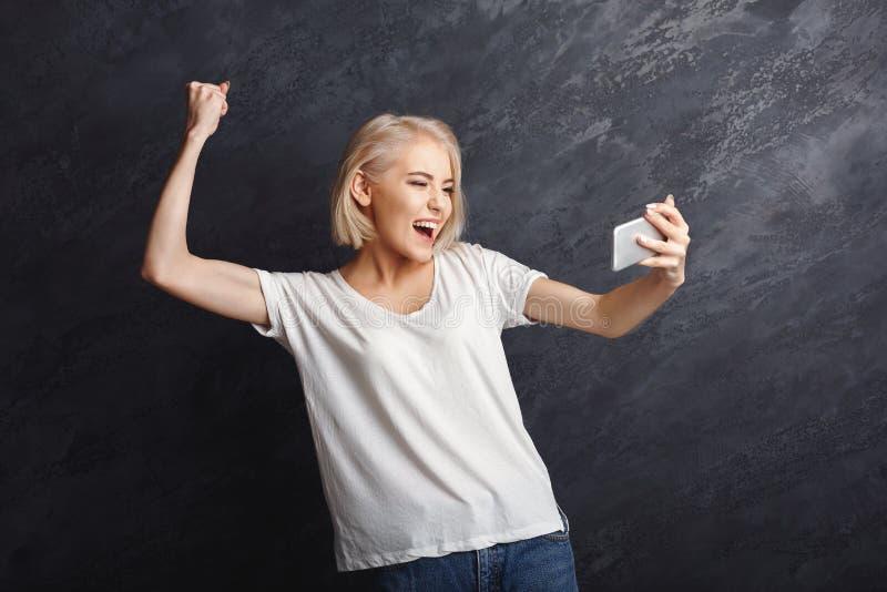 Läs- goda nyheter för lycklig flicka på mobil arkivfoton