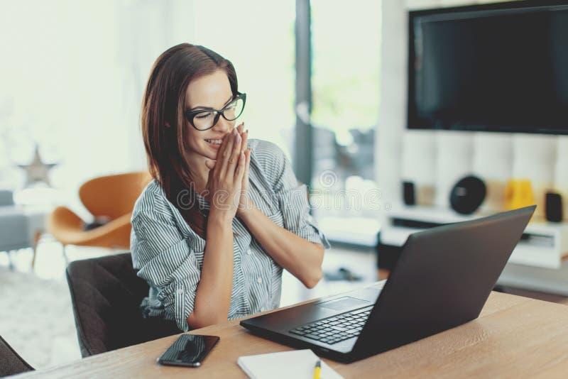 Läs- goda nyheter för lycklig ung modern affärskvinna på bärbara datorn arkivbild