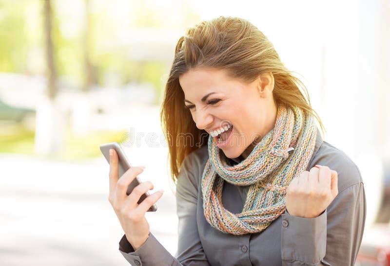 Läs- goda nyheter för upphetsad student på linje på mobiltelefonen utomhus royaltyfria foton