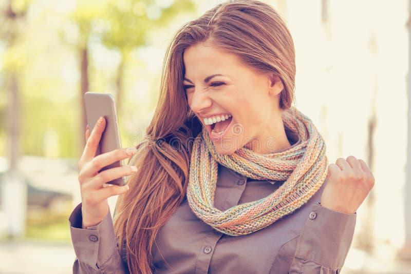 Läs- goda nyheter för upphetsad student på mobiltelefonen utomhus på en varm höstdag royaltyfri fotografi