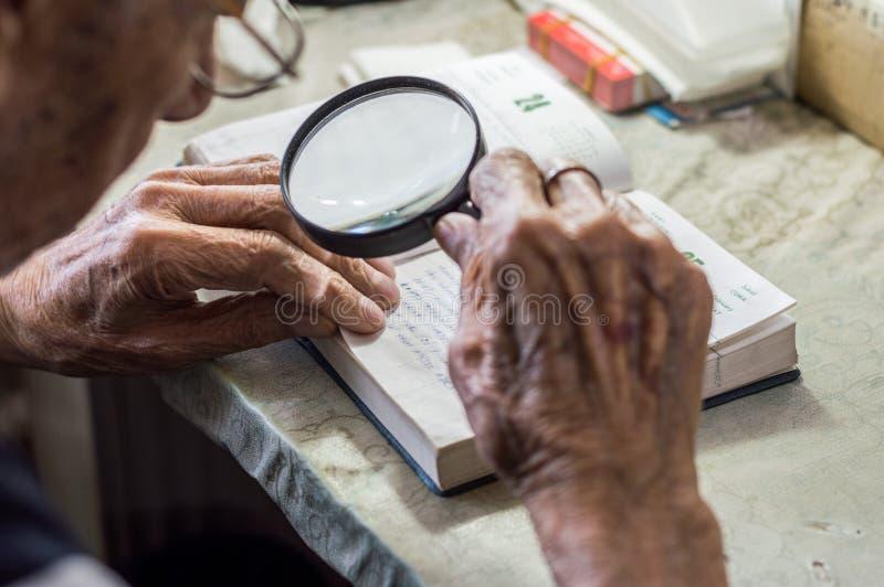Läs- handstilar för äldre man i en anteckningsbok med förstoringsglaset nära fönstret hemma arkivfoton