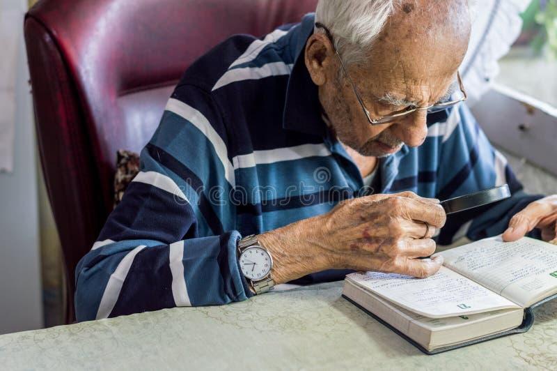 Läs- handstilar för äldre man i en anteckningsbok med förstoringsglaset nära fönstret hemma royaltyfri fotografi