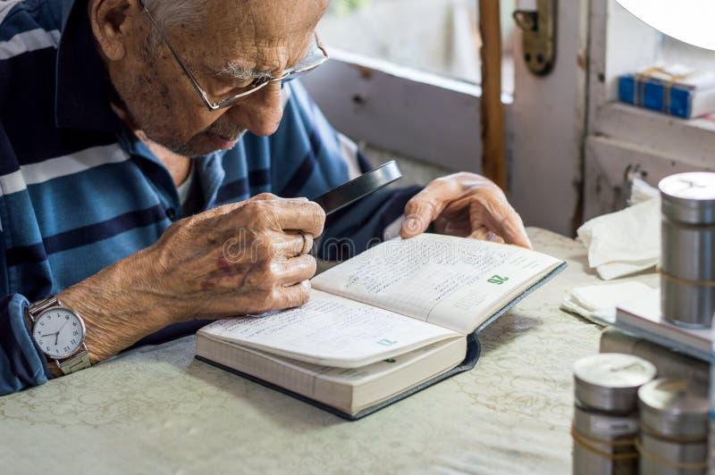 Läs- handstilar för äldre man i en anteckningsbok med förstoringsglaset nära fönstret hemma royaltyfria bilder