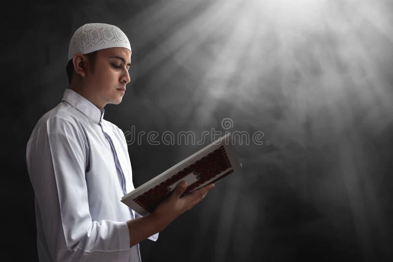 Läs- Koranen för muslimsk man royaltyfria foton