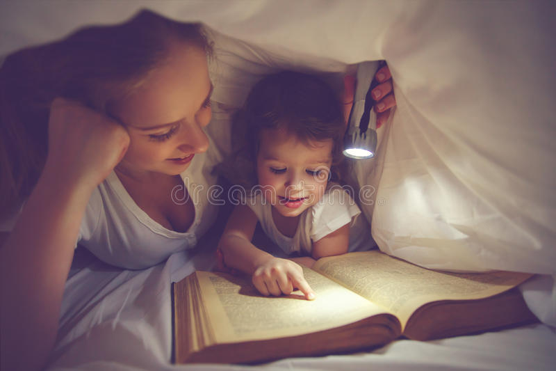Läs- läggdags för familj Mamma- och barnläsebok med en flashl royaltyfri fotografi