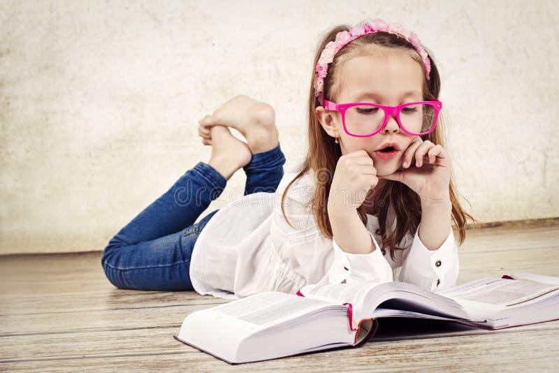 Läs- lärobok för nätt ung skolflicka och bärande exponeringsglas arkivfoto