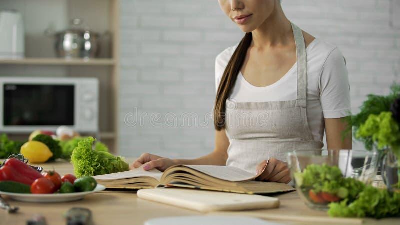 Läs- matlagningbok för asiatisk kvinna och välja matställereceptet, sund matvana royaltyfri bild