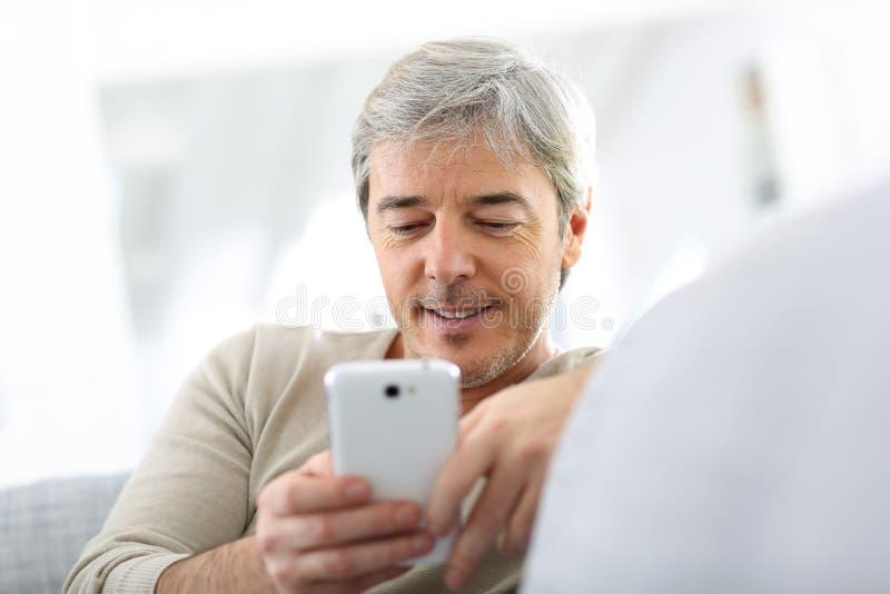Läs- meddelande för mogen man på smartphonen royaltyfri bild