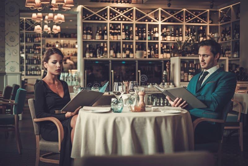 Läs- meny för par i en restaurang arkivfoto