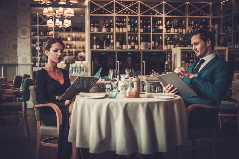 Läs- meny för par i en restaurang arkivbild