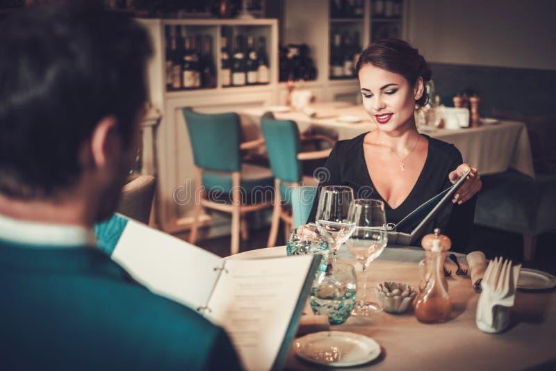 Läs- meny för par i en restaurang fotografering för bildbyråer