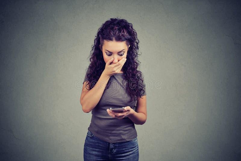 Läs- nyheterna för chockad kvinna på telefonen royaltyfria bilder