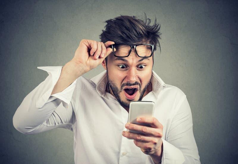 Läs- nyheterna för chockad man på smartphonen arkivbilder
