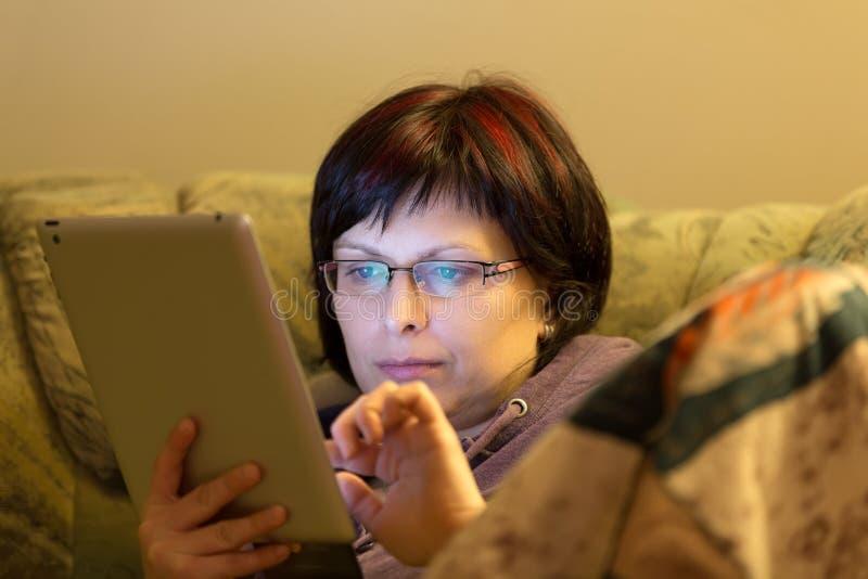Läs- nyheterna för kvinna på minnestavlan arkivbild
