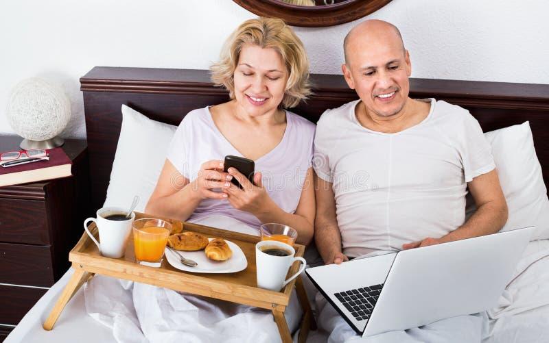 Läs- nyheterna för mogna positiva par från anteckningsboken fotografering för bildbyråer