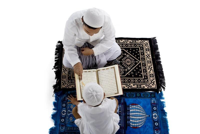 Läs- Quran för fader och för son tillsammans arkivfoton