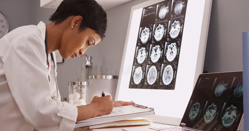 Läs- röntgenstråleresultat för afrikansk medicinsk kvinna av en hjärna arkivbilder