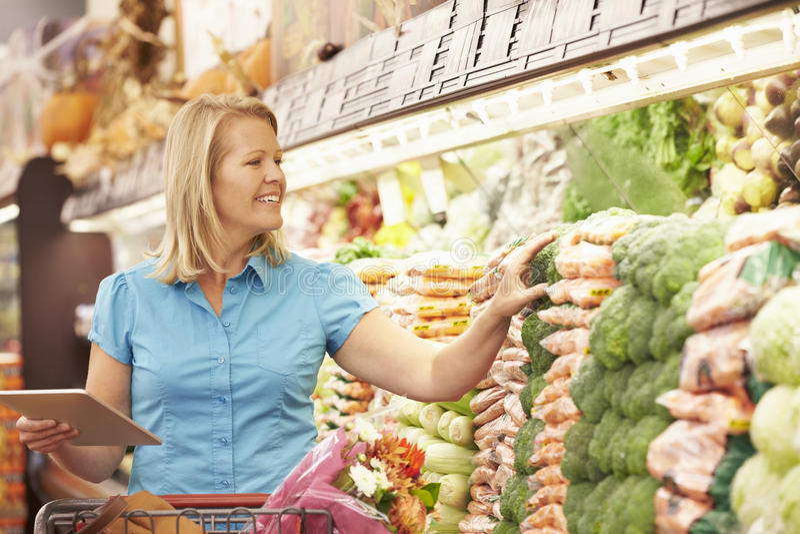 Läs- shoppinglista för kvinna från den Digital minnestavlan i supermarket fotografering för bildbyråer