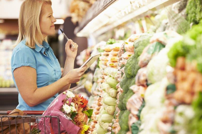 Läs- shoppinglista för kvinna i supermarket royaltyfri fotografi