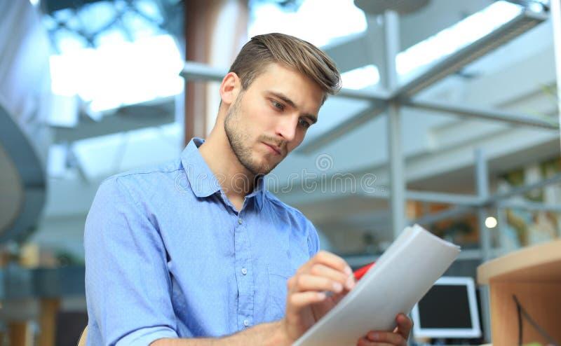 Läs- skrivbordsarbete för ung affärsman på skrivbordet i regeringsställning arkivbilder
