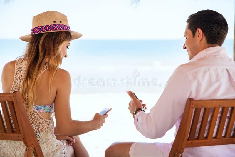 Läs- socialt massmedia för par på stranden arkivfoton