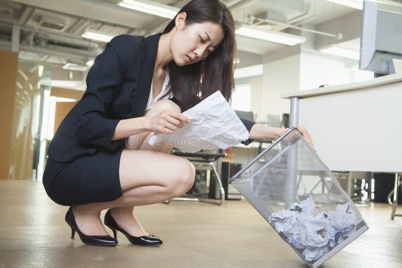 Läs- stycke för ung affärskvinna av papper från soptunnan i regeringsställning arkivbild