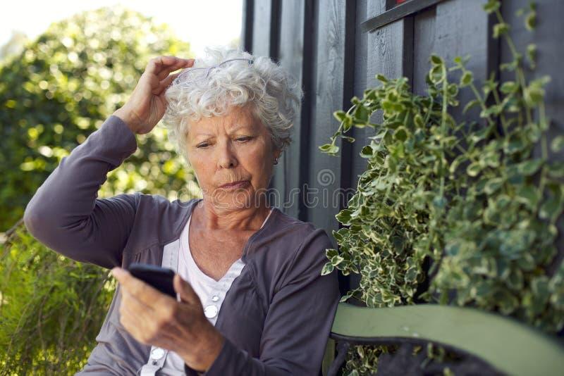 Läs- textmeddelande för äldre kvinna på hennes mobiltelefon arkivfoton
