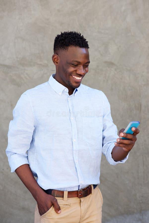 Läs- textmeddelande för modern ung svart man på hans mobiltelefon arkivfoton