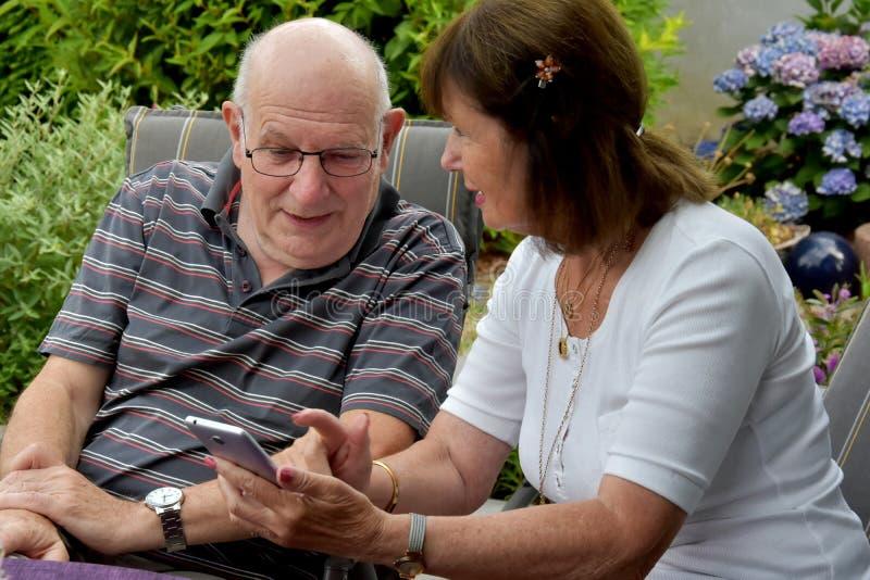 Läs- textmeddelanden för höga par på mobiltelefonen fotografering för bildbyråer