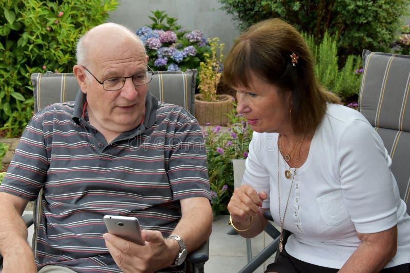 Läs- textmeddelanden för höga par på mobiltelefonen arkivbilder