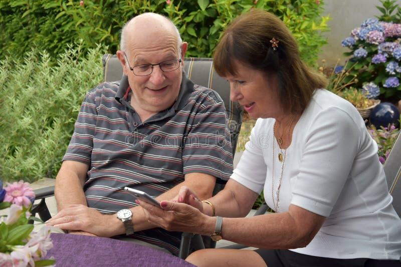 Läs- textmeddelanden för höga par på mobiltelefonen royaltyfri bild