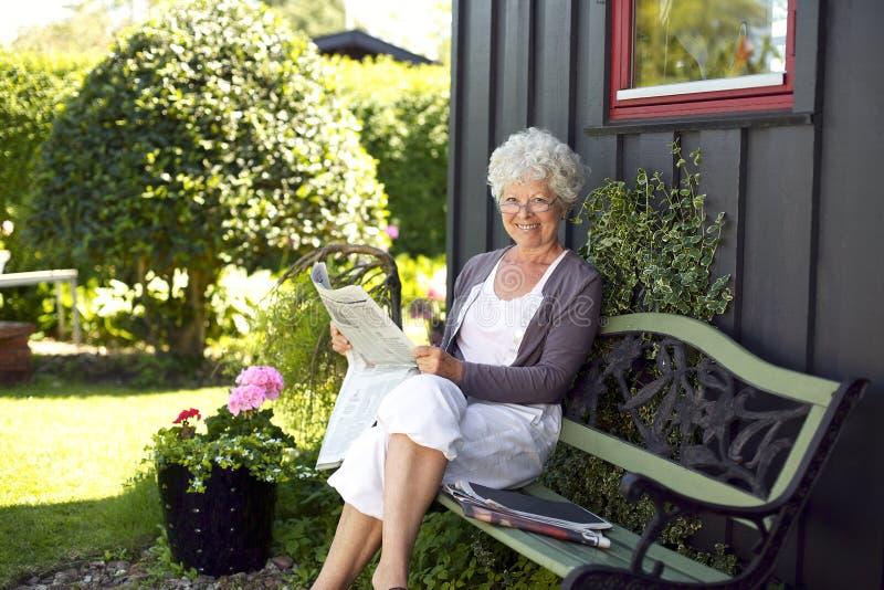 Läs- tidning för äldre kvinna i trädgårdträdgård arkivfoto