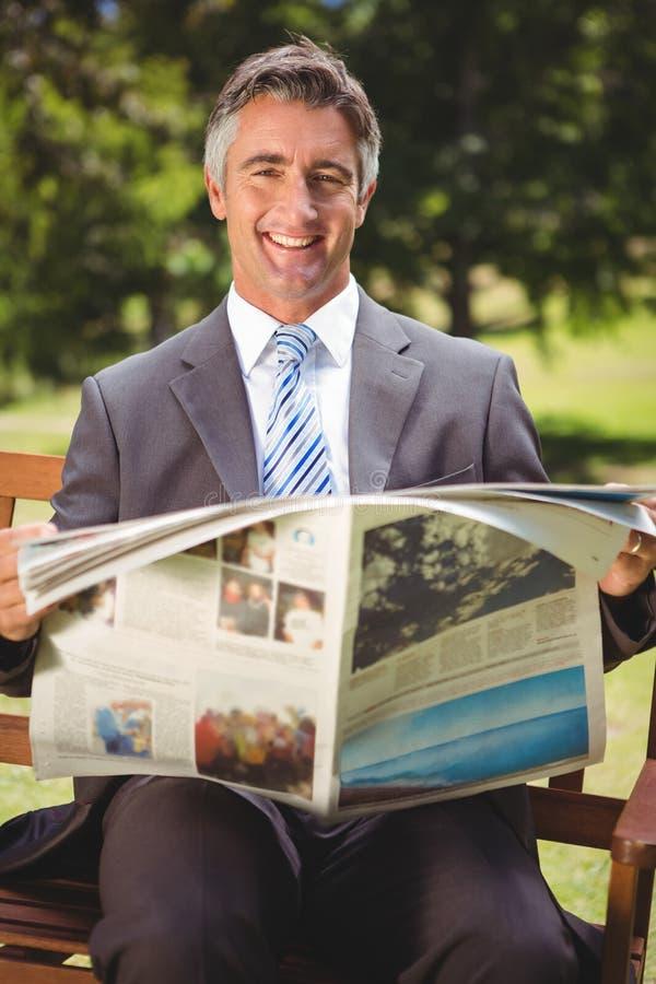 Läs- tidning för affärsman i parkera royaltyfria bilder