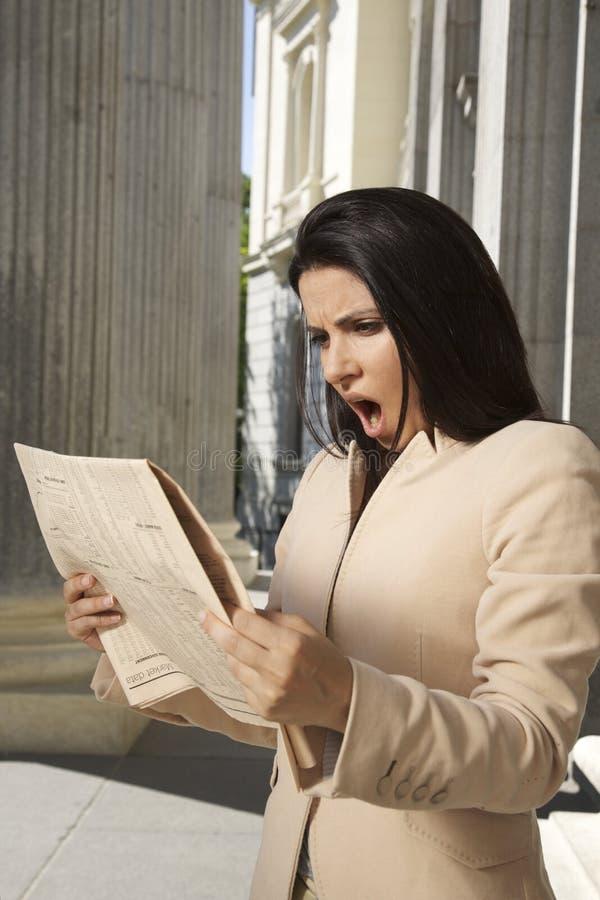 Läs- tidning för chockad affärskvinna royaltyfria foton