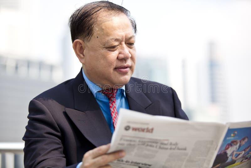 Läs- tidning för hög asiatisk affärsman fotografering för bildbyråer