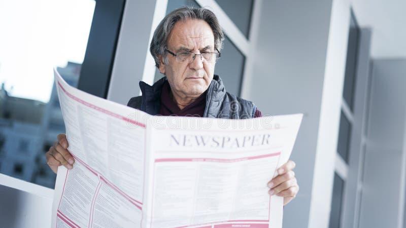 Läs- tidning för hög man i utomhus fotografering för bildbyråer