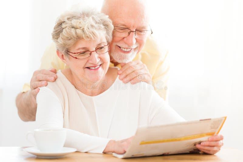 Läs- tidning för lyckliga och älskvärda höga par royaltyfria foton