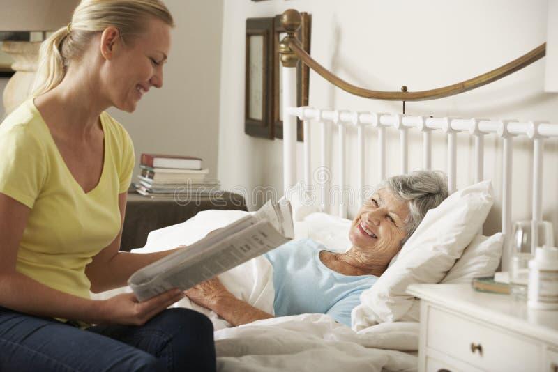 Läs- tidning för vuxen dotter till den höga kvinnliga föräldern i säng hemma arkivfoto