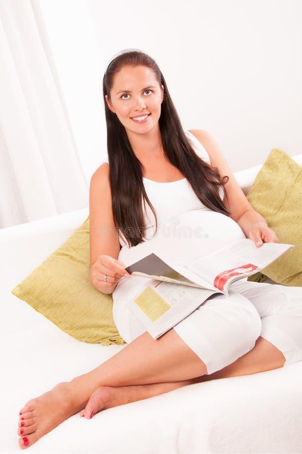 Läs- tidskrift för gravid kvinna på soffan hemma royaltyfri bild
